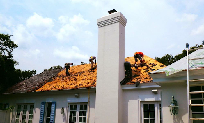 Three roofing contractors are replacing shingles on a home located in Trinity, Pasco County, FL.  Photo courtesy of Nations Roofing.
